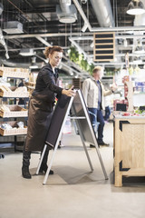 Owner adjusting blackboard while customer shopping in supermarket