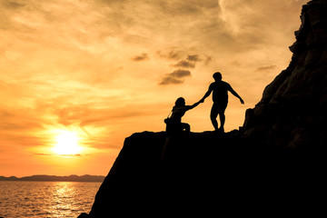 boy pull lady's hand for climb mountain during sunset