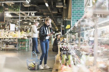 Girl using smart phone while reading label on bottle in organic groceries store