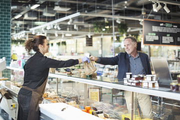 Side view of saleswoman giving package to mature man in organic supermarket