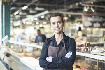 Portrait of confident female owner standing arms crossed in supermarket