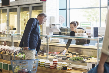 Saleswoman assisting mature man in buying groceries at supermarket