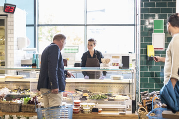 Mature man buying groceries from saleswoman in supermarket