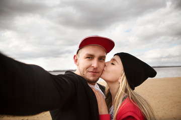 Two lovers making a selfie photo near the river..