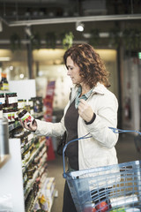Side view of woman reading label on bottle while shopping in supermarket