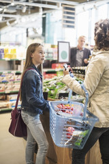 Girl looking at mother while shopping in organic supermarket