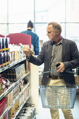 Mature man reading label on food package in supermarket