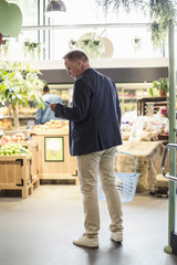 Rear view of mature man using smart phone in supermarket