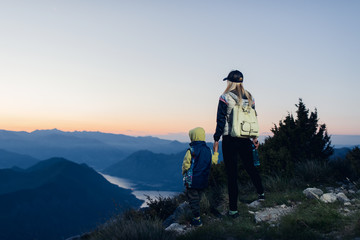 Woman with his son on a mountain top enjoying the view and a sunset