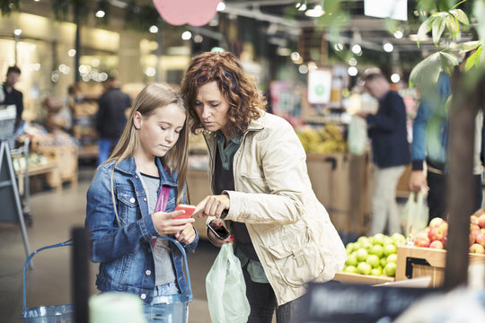 Mother and daughter using smart phone in organic grocery store