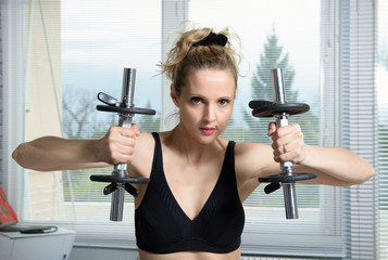 pretty fitness woman lifting dumbbells