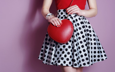 Wall Mural - Sweet stylish woman in polka dot dress with red bag. Close up