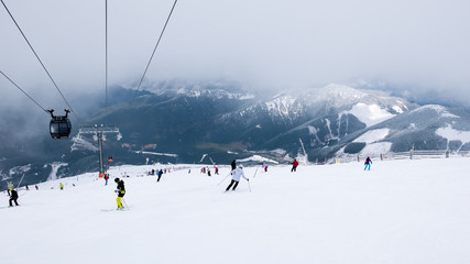Cable car and skiers on the slope in ski resort Chopok in Slovakia. Tatra lower mountains.