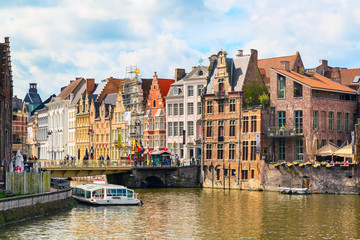 Old houses along canal and boats in popular touristic destination Ghent, Belgium