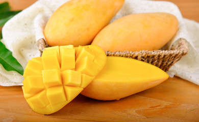 yellow mangoes on wooden background