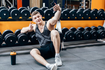 Image of happy young sportsman sitting in gym and make selfie.