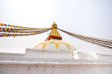Boudhanath stupa and its colorful flags in daylight.