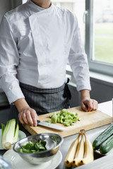 Crop faceless shot of male im uniform cutting celery on cutting board for preparing smoothie.