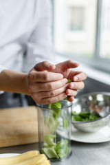 Crop hands of male chef putting cut celery in content for preparing fresh smoothie.