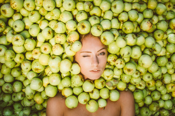 Portrait of beautiful girl that lies in the green apples