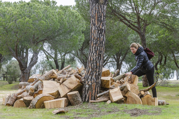 Woman next to logs of cut wood