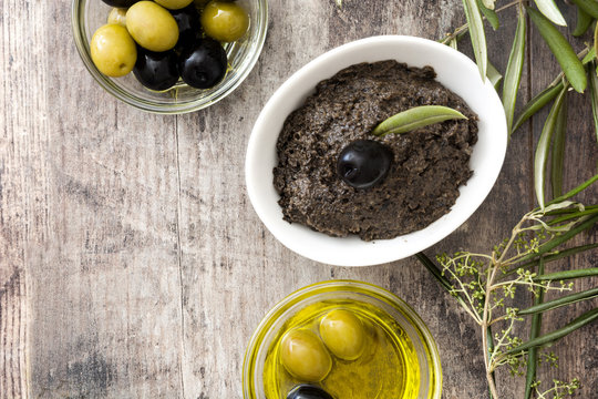 Black olive tapenade with anchovies, garlic and olive oil on wooden background