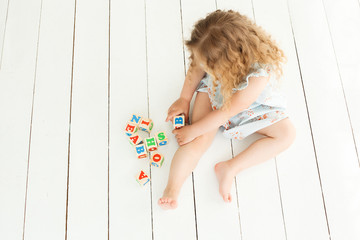 Little cute girl playing with abc cubes and educating. Pretty girl building an alphabet blocks. Child playing indoors.