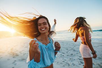 Female friends dancing on the beach