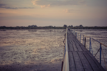 Wooden bridge over the estuary on the Black Sea at sunset, the bridge on the right