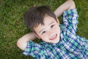 Mixed Race Chinese and Caucasian Young Boy Relaxing On His Back Outside On The Grass