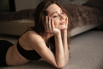 Smiling relaxed woman lying with eyes closed on the floor