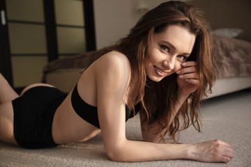 Happy seductive young woman lying on the floor in bedroom
