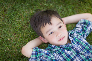 Thoughtful Mixed Race Chinese and Caucasian Young Boy Relaxing On His Back Outside On The Grass