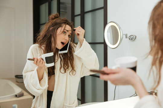 Woman doing makeup and talking on cell phone in bathroom