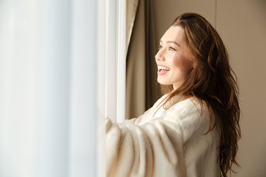 Cheerful woman in bathrobe smiling and looking at the window