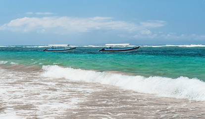 beach in Bali with sea views with two boats with a line of surf on a Sunny day with clouds on the horizon horizontal view