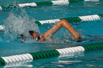 Young boy swimming a competitive freestyle swim race with green and white lane markers