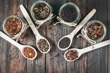 Different kinds of tea in jar and wooden spoons on wood table