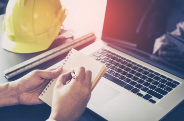 Engineer is making plan on blank notebook in office