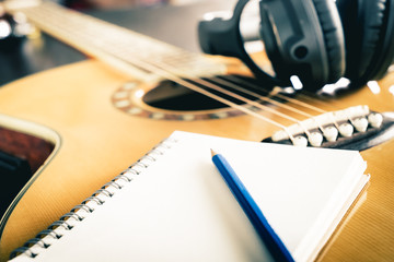 Guitar and Headphone with blank notebook for songwriting