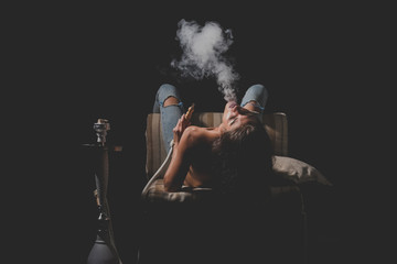sexy girl with naked body smoking hookah in jeans