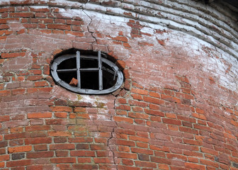 The red brick wall with the small round window of the old tower in Orel Region in Russia
