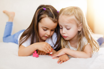 Two little girls painted their nails at home