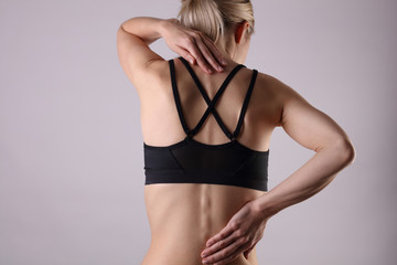 Athletic woman suffering from back pain . Pain relief, chiropractic concept. Sport exercising injury