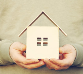 House from paper in the man's hands. Conceptual image of protection of the house, sale or acquisition of the house