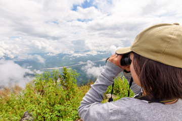 Woman tourist are using binoculars to see the beautiful natural landscape of the sky forest and mountain near the Mekong River at Doi Pha Tang view point in Chiang Rai Province, Thailand