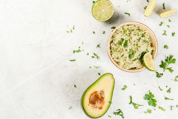Homemade guacamole in bowl, served with lime lemon and parsley, with half of avocado on white concrete table. Top view copy space