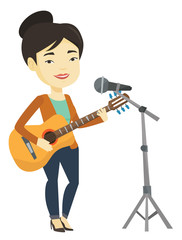 Woman singing in microphone and playing guitar.