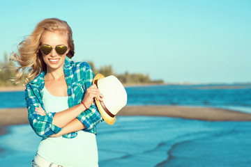 Portrait of young gorgeous sexy suntanned blond wearing mirrored heart shaped sunglasses and checked blue shirt standing at the seaside with the hat in her hand, her hair blown by the wind. Copy-space