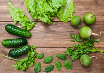 Green vegetables and salad on a wooden background. Top view with space for text